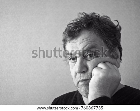 Black and white photo of sad middle aged caucasian man