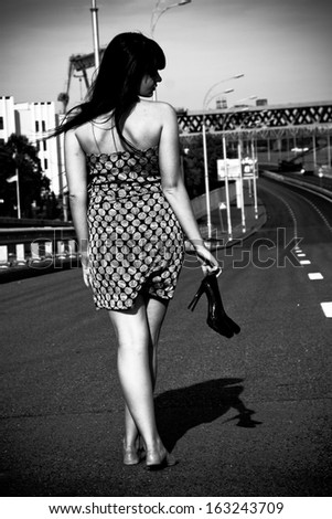Black and white photo of sexy barefoot woman walking on highway and holding shoes in hand - stock photo