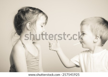 black and white photo of siblings playing with each other's lollipops - stock photo
