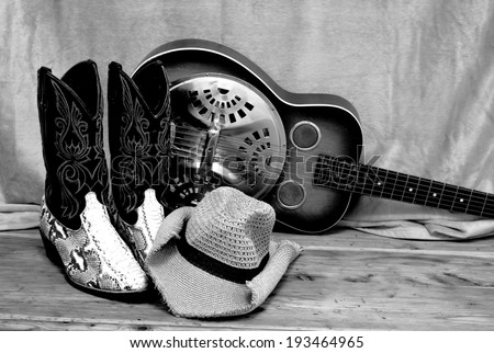 black and white photo of snakeskin cowboy boots with a cowboy hat and a vintage dobro resonator guitar. The country western themed items are on a rustic wooden surface. The snakeskin is python. - stock photo