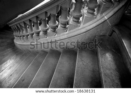 Black and white photo of spiral marble staircase leading downward