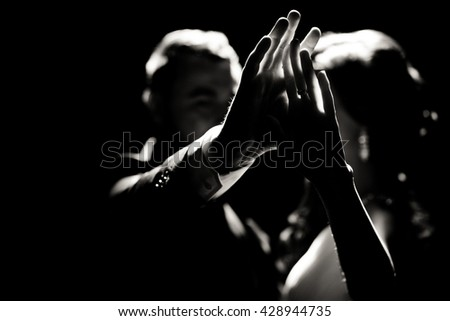 Black and white photo of the hands of the couple - stock photo