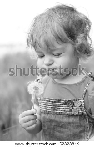 Black and white photo of the little girl blowing on dandelion - shallow depth of field - stock photo