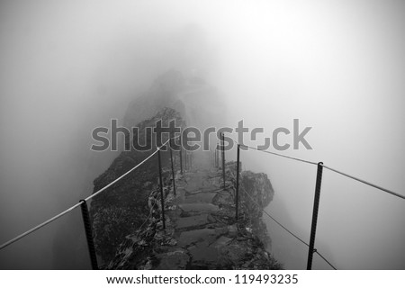 Black and white photo of the path to the Pico Ruivo and Pico do Areeiro mountain peaks in a fog in Madeira, Portugal. A mystic path, road to nowhere
