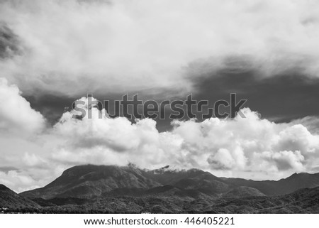 Black and white photo of the tops of mountains under the beautiful volume clouds.