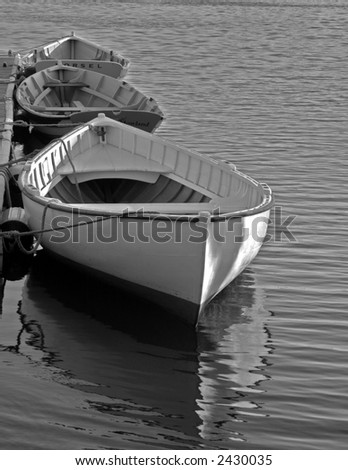 Black and white photo of three boats moored on the Mystic River in Connecticut - stock photo
