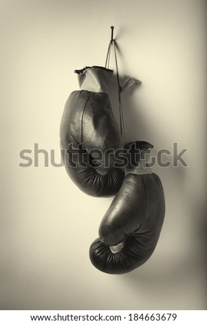 Black and white photo of vintage boxing gloves. - stock photo