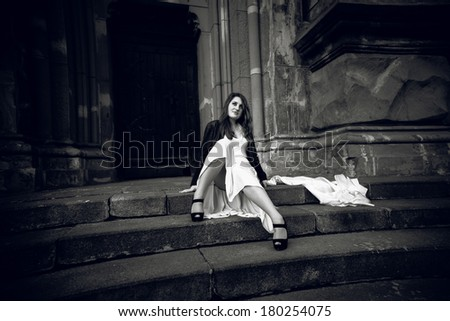 Black and white photo of woman in long dress sitting on stone stairs at castle - stock photo