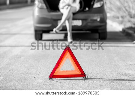 Black and white photo of woman sitting on broken car near red warning sign - stock photo