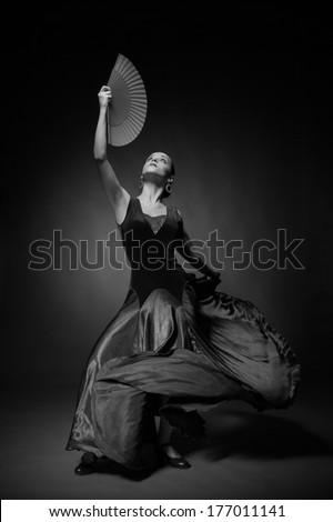 Black and white photo of young woman dancing flamenco - stock photo