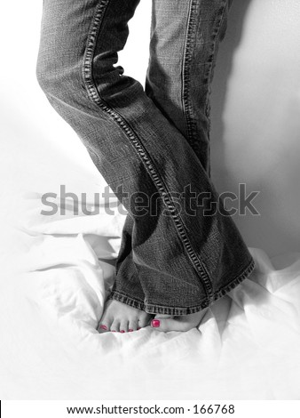 Black and white photo of young woman in jeans with bright pink toenail polish