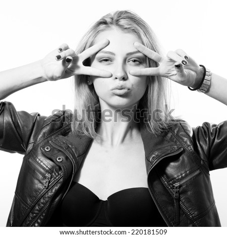 black and white photo portrait of blond young woman beautiful sexy provocative girl in black leather jacket having fun looking at camera and showing V-sign on light copy space background - stock photo
