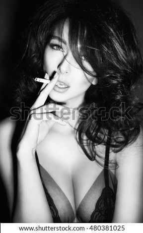 black and white photo portrait of sexy young woman with beautiful body smoking a cigarette in lingerie on black background