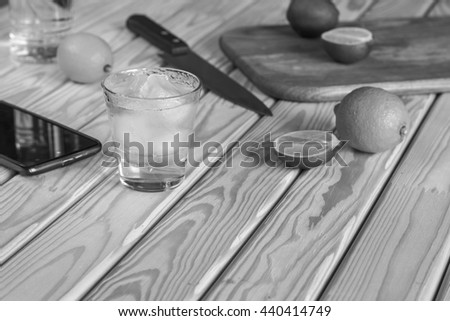 black and white photo. Square shot. Cocktail vodka or gin is reflected in the tablet computer. vintage, tequila. - stock photo