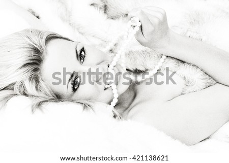 Black and white photograph beautiful young blond woman or girl in bed wrapped in (fake) fur and biting a pearl necklace - stock photo