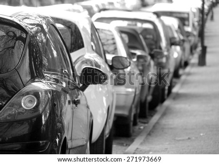 Black and white photograph of cars parked in city centre - stock photo