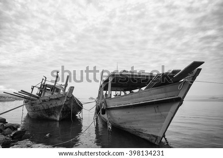 Black and white photograph of two old wooden fishing boat anchored by the shore - stock photo