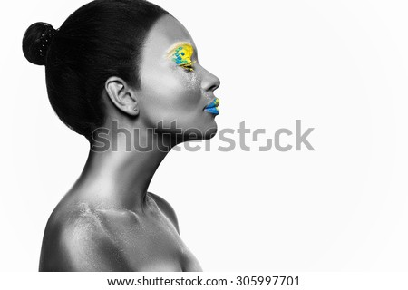 Black and white photograph of young beautiful dark skinned woman with vividly yellow-blue make up