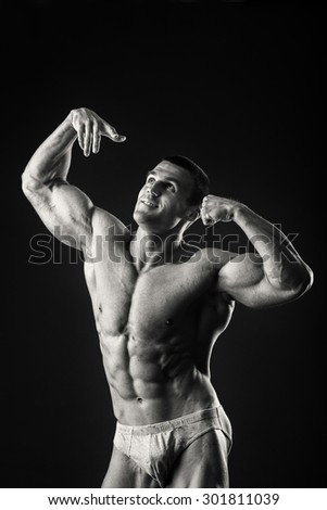 Black and white photography. Handsome muscular guy, bodybuilder, posing on a black background. Traced muscles, posing, sports, muscle power - the concept of sport of bodybuilding. - stock photo
