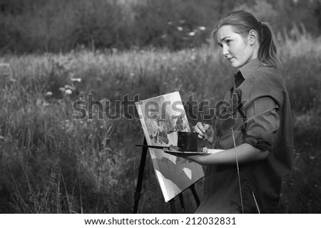 Black-and-white photography of a young girl-artist painting with watercolor on the plein air - stock photo