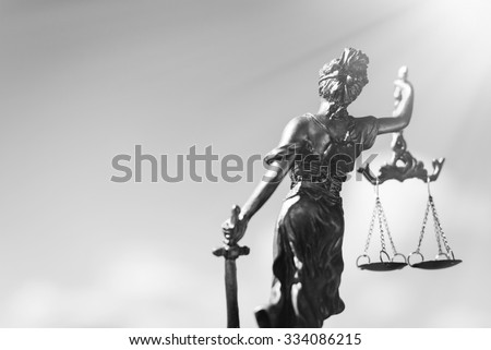 Black and white photography of back of sculpture of themis, femida or justice goddess on bright sky copyspace background - stock photo