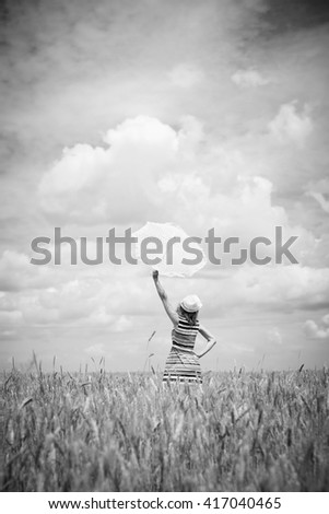 Black and white photography of beautiful amazed young woman holding umbrella, background copyspace - stock photo