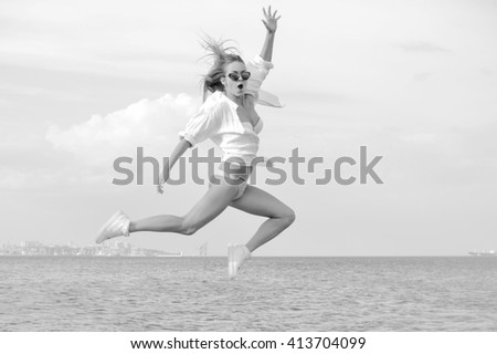 Black and white photography of beautiful young lady enjoying dancing jumping over outdoors water sky background. Portrait of sporty girl - stock photo