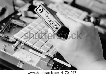Black and white photography of hands fixing broken computer part, concept of technology - stock photo