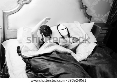 Black and white photography of sexy beautiful young models dolls in carnival masks having fun in bed relaxing