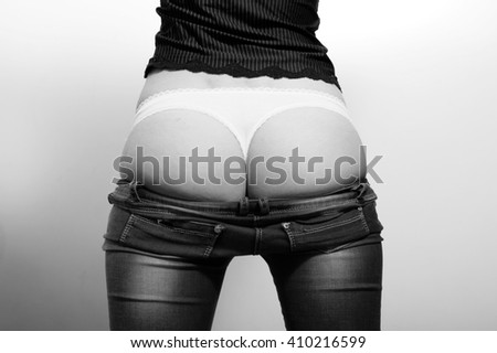 Black and white photography of sexy female buttocks in underwear on light background. Back view of undressing jeans, close up photo