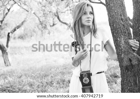 Black and white photography of young beautiful blond woman with retro camera in summer nature background, portrait  - stock photo