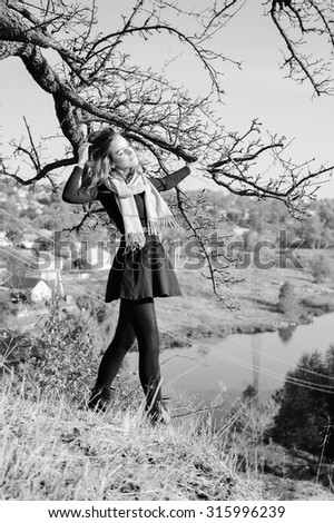 Black and white photography of young pretty lady standing at tree by river and having fun relaxing on outdoors background copy space