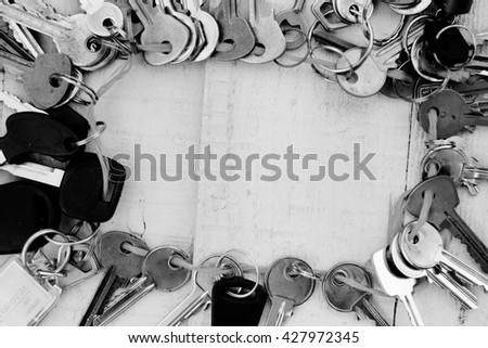 Black and white photography top view - Chain of keys on wooden background copyspace as symbol of security - stock photo
