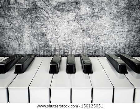 black and white piano keys on a stucco wall - stock photo