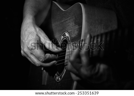 Black and white Picture . Close up of a guitarplayer . The Hand of the player looking aged. High contrast.  - stock photo