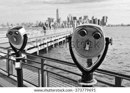 black and white picture of antique binoculars on Liberty Island with view to Manhattan, New York City - stock photo