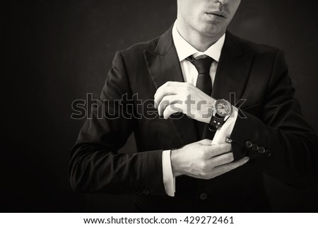 Black and white picture of business man fixing his shirt - stock photo