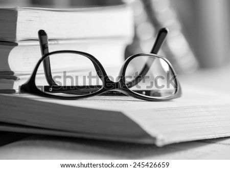 Black and white Picture of glasses on a book. High contrast. - stock photo