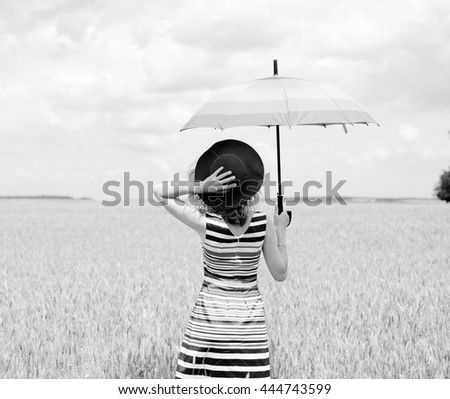 Black and white picture of joyful dreamer enjoying her life with raised hands to the sky. Lady hold umbrella and hat on the field background