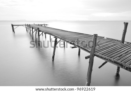 black and white picture of old bridge to the sea. - stock photo