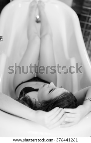 Black and white picture of sexy beautiful young lady having fun relaxing in bath tub - stock photo