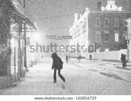 Black-and-white picture of the city street during a snow-storm. Some pedestrians hurry to take cover from a wind. - stock photo