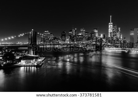 black and white picture of the skyline of downtown Manhattan with Brooklyn Bridge and East River in New York City at night - stock photo
