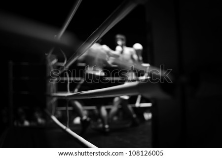 Black and white picture of two sportsmen boxing on square. - stock photo