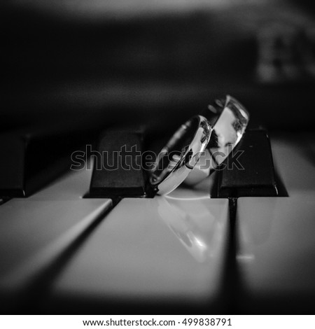 Black and white picture of wedding rings lying over the piano keys