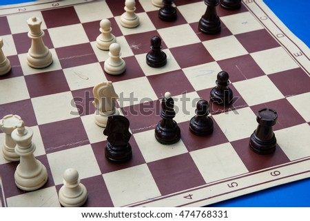 Black and white plastic chess pieces on a cheap paper chess board. The game is under way. Open air chess competitions.