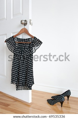 Black and white polka dot blouse on a hanger and shoes on wooden floor. - stock photo