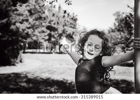 Black and white portrait happy child with hand up, enjoying freedom at summer park. Freedom concept. - stock photo