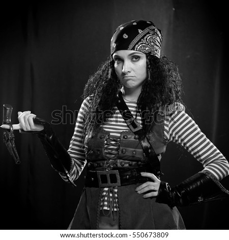 black and white portrait of a actress woman in a pirate costume with a gun on a blue-black background