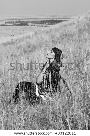 Black and white portrait of a beautiful bohemian woman seated outside in a field of grass. - stock photo
